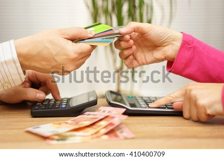 man and woman are calculating how will they spend their tight salaries and which credit card they will use - stock photo