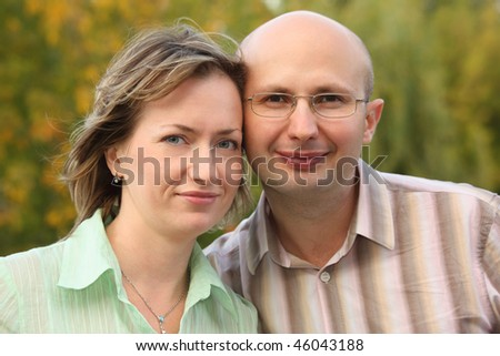 man and woman are cuddling in early fall park and looking at camera