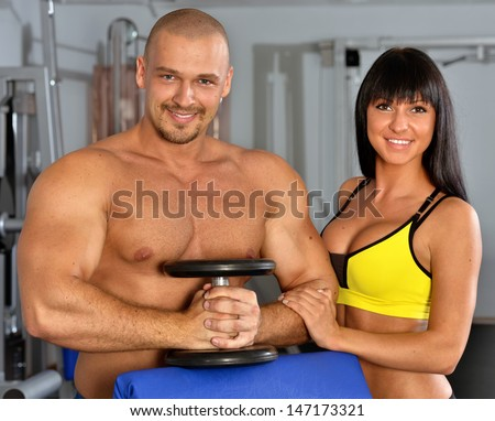 Man and woman are doing exercises in a sport club.