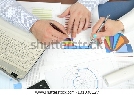 man and woman are examining statistics at the office - stock photo