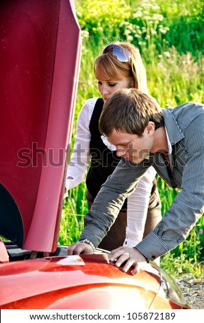 Man and woman are looking at the car engine