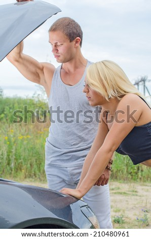 Man and woman are looking at the car engine. - stock photo