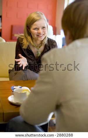 Man and woman are sitting at the cafe's table and having good time. Short depth of focus on woman's face. - stock photo