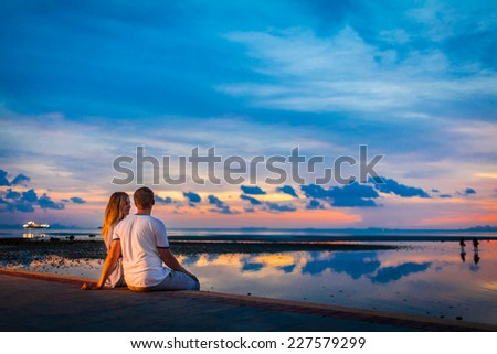 Man and woman are watching a sunset. - stock photo