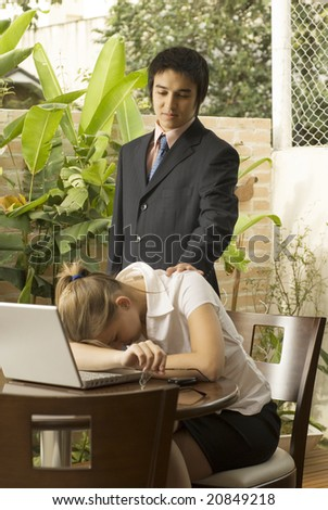 Man and woman at a desk with a laptop computer. He is comforting her as she lays her head on the table. Vertically framed photo. - stock photo