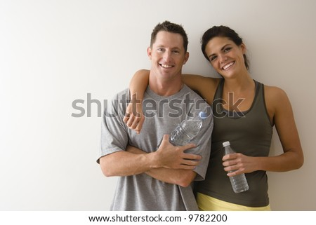 Man and woman at gym in fitness attire holding water bottles standing against wall smiling. - stock photo