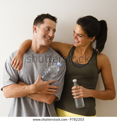 Man and woman at gym in fitness attire holding water bottles standing against wall smiling at eachother. - stock photo