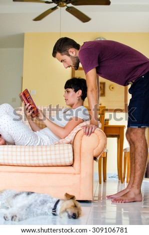 Man and woman at home. Woman on the sofa reading book. - stock photo