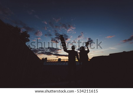 Man and woman at sunset. Silhouettes.