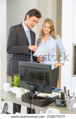 Man and woman at the office reading a document - stock photo