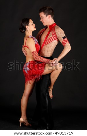 Man and woman ballroom dancers in exotic costumes perform acrobatic dance against black background - stock photo
