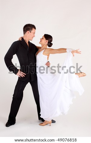 Man and woman ballroom dancers in long white gown and black suit perform before a white background - stock photo