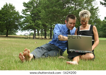 Man and woman barefoot in grass working on laptop.