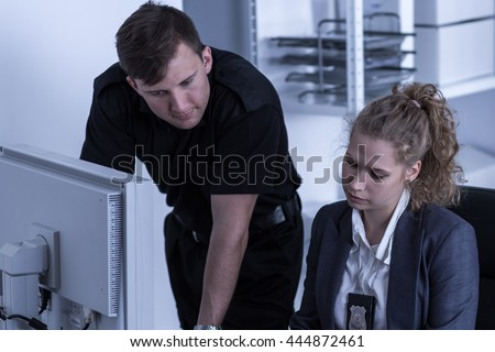 Man and woman beside computer, working at a police station  - stock photo