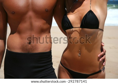 Man and woman body on the beach - stock photo