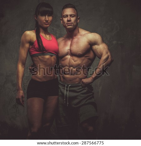 Man and woman bodybuilders couple posing on grey background - stock photo