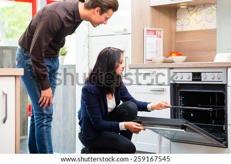 Man and woman buying domestic kitchen in studio or furniture store showroom - stock photo