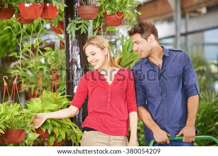 Man and woman buying plants together in a garden center - stock photo