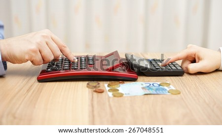 man and woman calculating hot to split little money, concept of poverty - stock photo