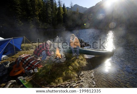 Man and woman camping on small island - stock photo