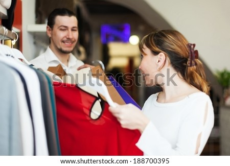 Man and woman choosing clothes at clothing store