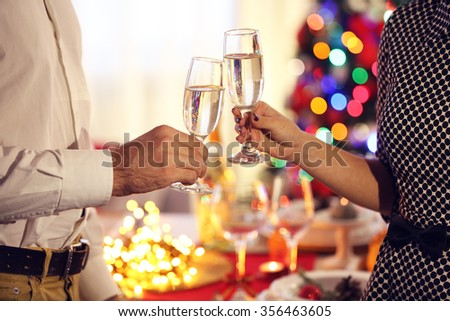 Man and woman clanging champagne glasses on Christmas background
