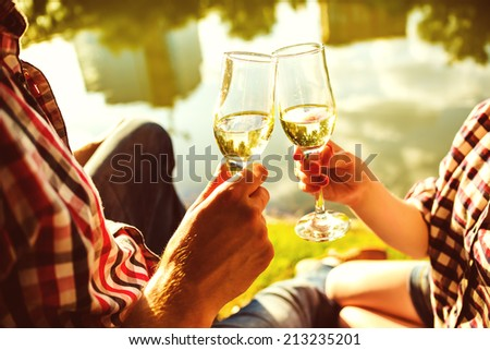 Man and woman clanging wine glasses with champagne - stock photo
