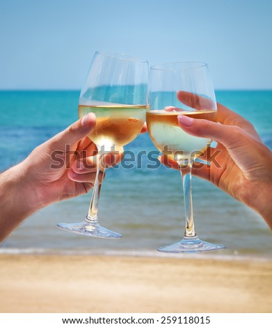 Man and woman clanging wine glasses with white wine at sky and sea background - stock photo