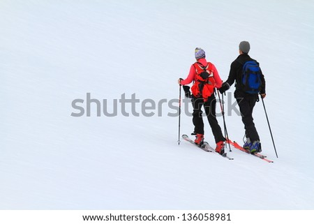 Man and woman climbing a snowy slope on ski - stock photo
