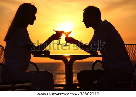 man and woman clink glasses on sunset outside - stock photo