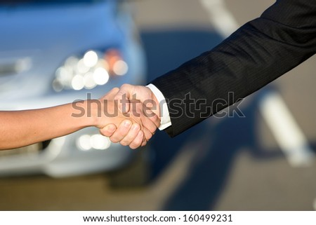 Man and woman closing a car sale agreement with a handshake. Salesman and buyer shaking hands - stock photo