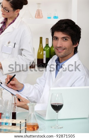 Man and woman conducting experiment on wine - stock photo