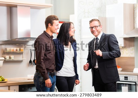Man and woman consult salesman for domestic kitchen in studio or furniture store - stock photo