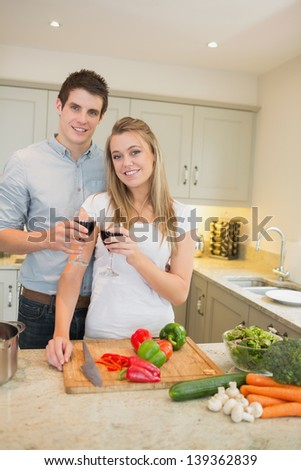 Man and woman cooking and clinking wine glasses in kitchen - stock photo