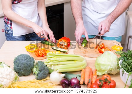 man and woman cooking together raw vegetables