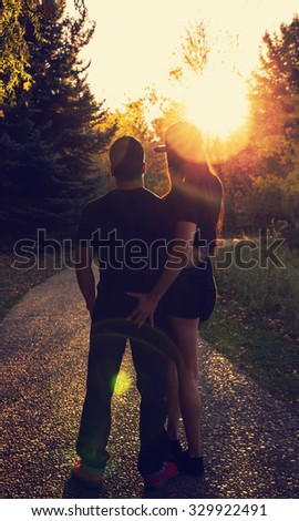 man and woman couple silhouette facing down the path into a sunset with a retro toned instagram filter - stock photo