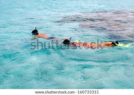 Man and woman couple snorkeling in Aitutaki Lagoon, Cook Islands