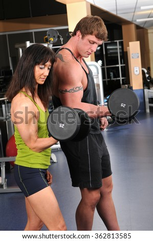Man and woman curling dumbbell inside gym
