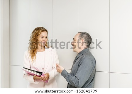 Man and woman discussing work in business office hallway - stock photo
