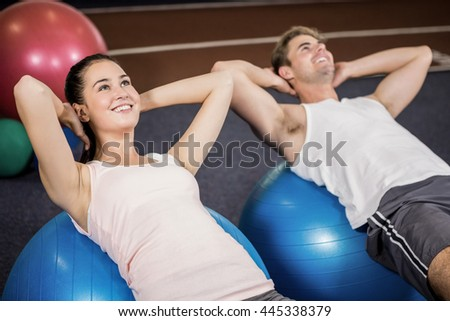 Man and woman doing abdominal crunches on fitness ball at gym - stock photo