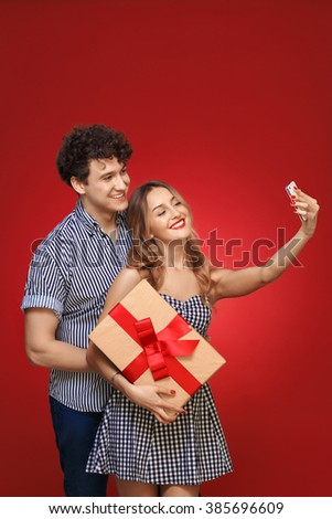 man and woman doing selfie phone Pin Up with a gift in style, isolated on a red background.