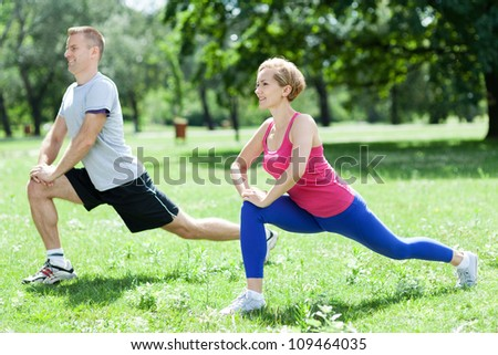 Man and woman doing stretching exercises - stock photo