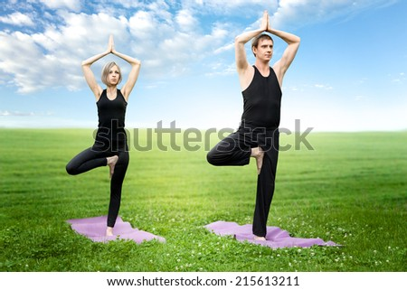 Man and woman doing yoga meditating in tree position - stock photo