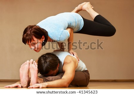 man and woman doing yoga practice indoors - stock photo
