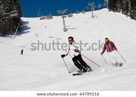 Man and woman downhill skiing on wide piste in alps mountains - stock photo