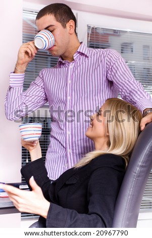 man and woman drinking coffee at the office - stock photo