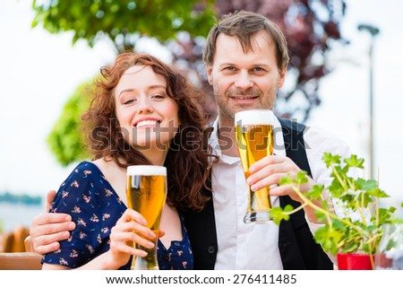 Man and woman drinking in beer garden pub