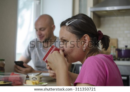"""Man and woman drinking tea in the kitchen. """"Real People"""" series - stock photo"""