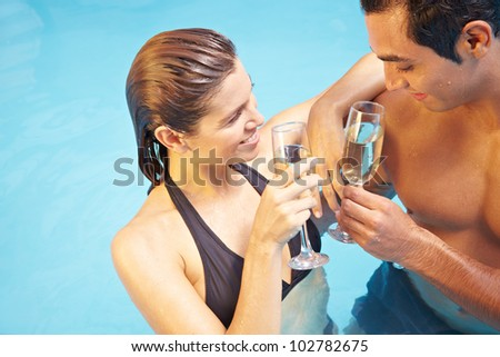 Man and woman drinking together glass of champagne in swimming pool