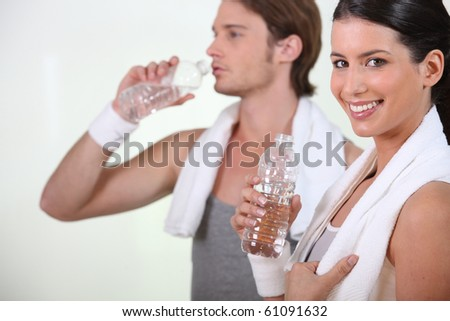 Man and woman drinking water after sports